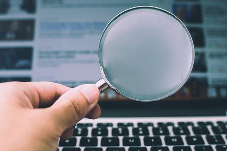 Vergrootglas met de laptop achtergrond.