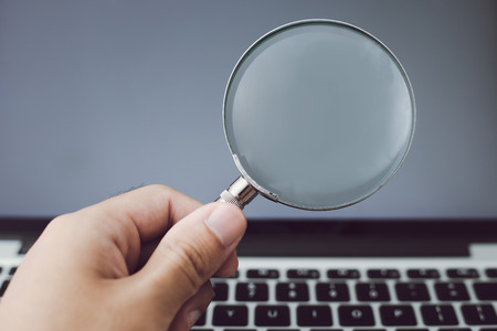 Magnifying glass with the laptop background. Stock fotó