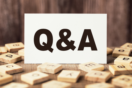 Q and A sign on the wooden table with wooden background.