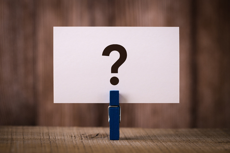 Question Mark sign on the wooden table with wooden background.