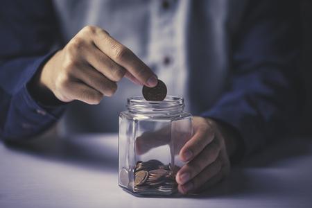 Mano de hombre poniendo dinero en botella de vidrio. Foto de archivo