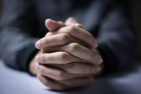 El hombre está rezando con las manos juntas.