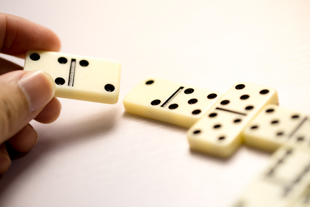 Playing dominoes on a white wooden table.