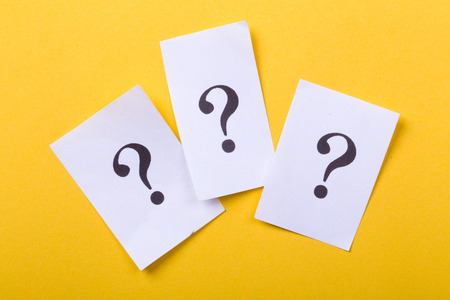 White paper with question mark against yellow background.