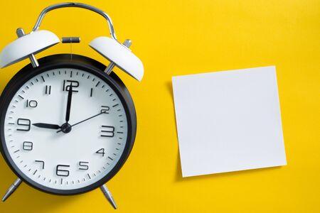 Despertador sobre fondo de color amarillo con nota adhesiva de espacio de copia en blanco.