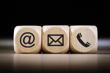 Contact Methods. Close-up of a phone, email and post icons wooden block. Foto de archivo