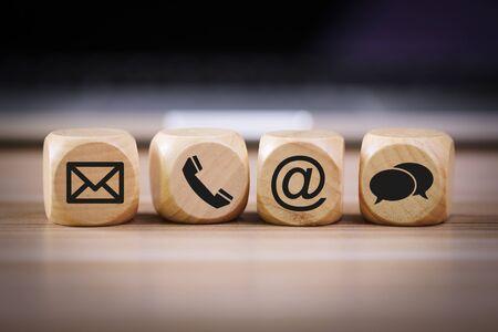 Métodos de contacto. Primer plano de un bloque de madera de los iconos de teléfono, correo electrónico, chat y publicación.