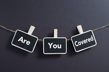 Small blackboards with Are You Covered concept is hanging on line.