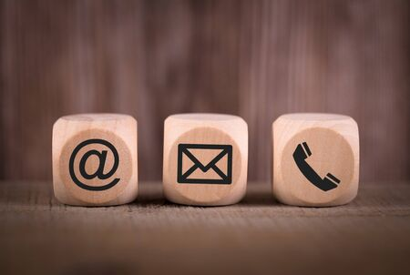 Contact Methods. Close-up of a phone, email and post icons wooden block. Banco de Imagens