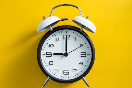Black alarm clock on yellow color background.