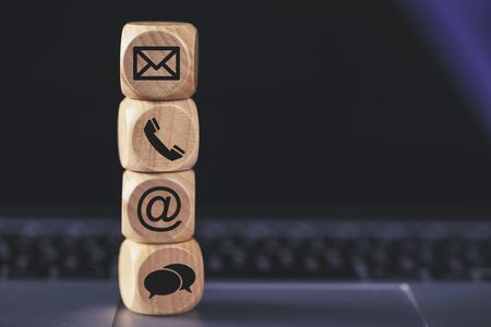Contact Methods. Close-up of a phone, email, chat and post icons wooden block. Banco de Imagens
