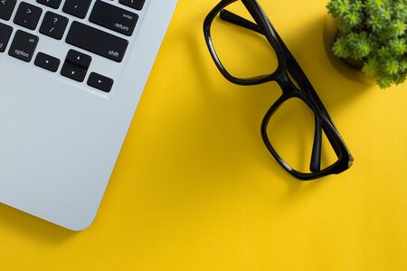 Topview of yellow office desktop with black glasses, laptop keyboard, green plant. Banco de Imagens