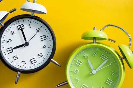 Black and green alarm clocks on yellow color background. Banco de Imagens