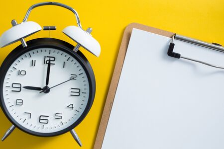 Alarm clock on yellow color background with blank white copy space.