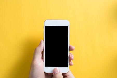 Smartphone vuoto con mano isolata su sfondo giallo. Archivio Fotografico