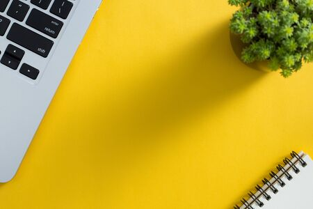 Topview of yellow office desktop with laptop keyboard, green plant and notepad. Banco de Imagens