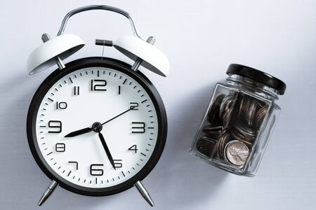 Alarm clock and a bottle of coins on yellow color background.