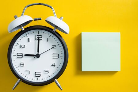 Alarm clock on yellow color background with blank white copy space sticky note.