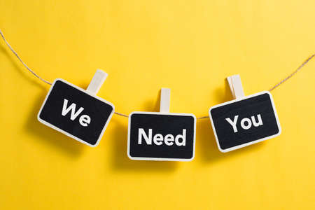 We Need You concept small blackboard hanging on line. Stock Photo