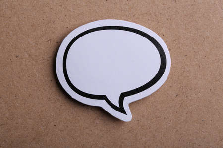 White blank speech bubble isolated on brown paper background with shadow.