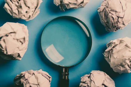 Magnifying with crumpled paper ball on the blue background.