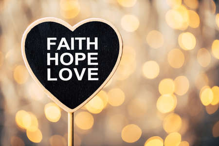 Faith Hope And Love heart shape blackboard against beautiful shiny background. Stock Photo