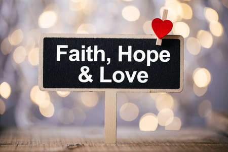 Faith Hope And Love blackboard with red heart against beautiful shiny background. Stockfoto