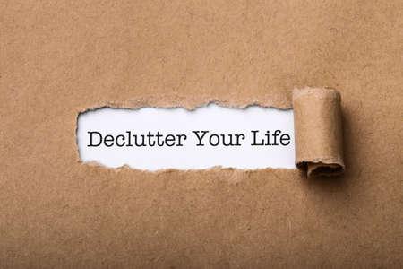 Declutter Your Life Concept word written under torn paper.