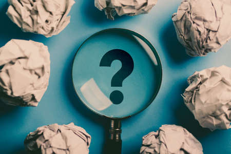 Question Mark Magnifying with crumpled paper ball on the blue background. Banque d'images