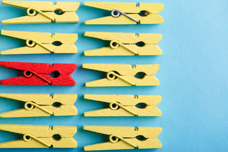 Stand out from the crowd and different concept. Leadership and other similar concepts. One red clothespin stands out from other yellow clothespins on blue background.