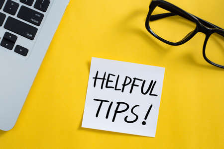 Helpful Tips concept on desktop workspace with office supplies.