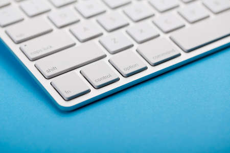 Closeup Shot Of White Keyboard on blue background.