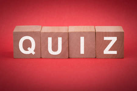 Quiz concept wooden blocks isolated on red background.
