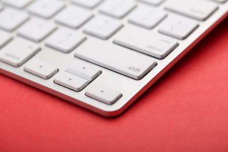 Closeup Shot Of White Keyboard on red background. 스톡 콘텐츠