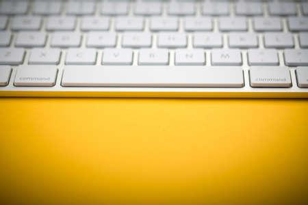 Closeup Shot Of White Keyboard on yellow background.