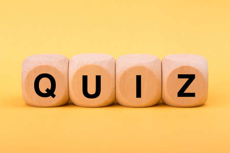 Quiz concept wooden blocks isolated on yellow background.