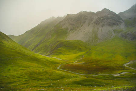 High light in the german alps with green hills and a cloudy mountain top 写真素材