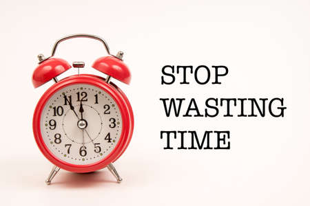 running out of time: alarm clock with stop wasting time text