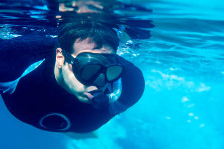 Man with snorkel swim in clear waters at Tenerife Canary Islands