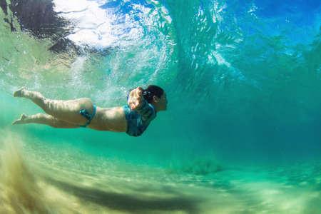 Frau schwimmt unter einer brechenden Welle am Strand von Fernando de Noronha in Brasilien Standard-Bild