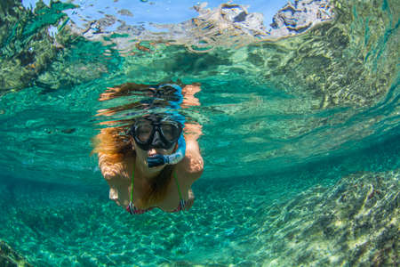 Woman swim with snorkel in crystal waters at Tenerife Canary Islands Spain