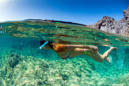Woman swim with snorkel in clear waters at Tenerife in Canary Islands Spain