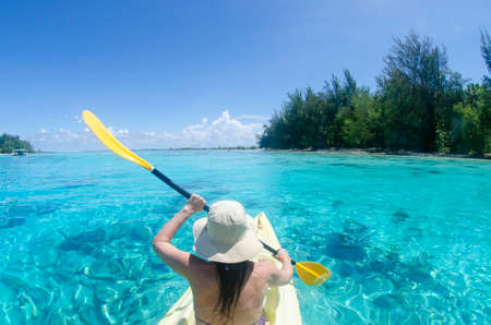 Woman paddle in yellow kayak in crystal clear waters at Moorea in Tahiti French Polynesia