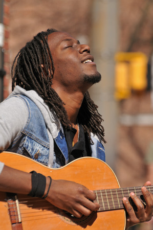 young African American musician playing guitar outside Stock Photo