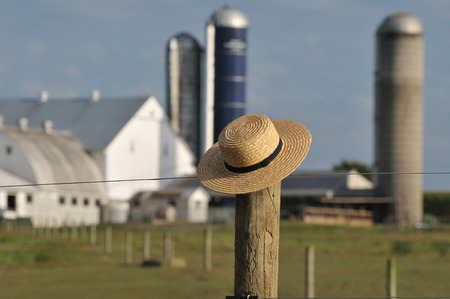 amish: Amish straw hat laying over fence post with Amish farm behind in the background