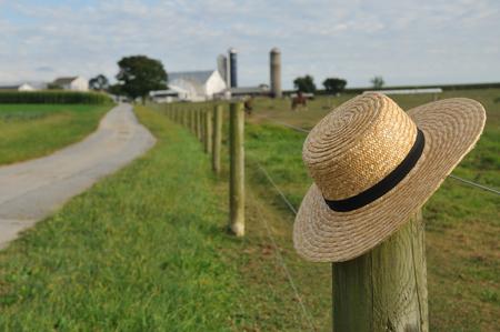 Close-up van Amish strooien hoed over de boerderij hek post