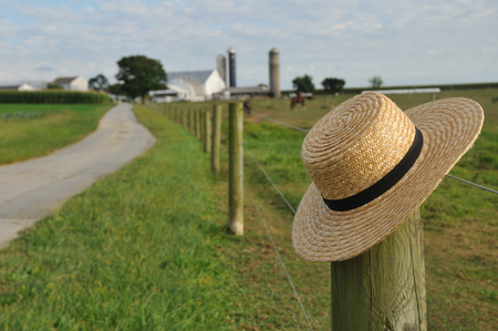 amish: closeup of Amish straw hat laying over farm fence post