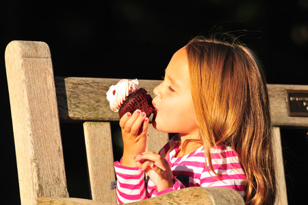 red velvet cupcake: little girl eating a red velvet cupcake with cream cheese icing