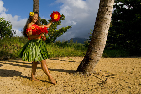 Hawaiian teenage girl dancing Hula on the beach in Kauai