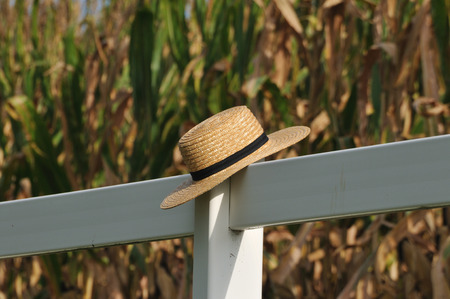 amish: Closeup of Pennsylvania dutch Amish hat laying over white fence post with corn field behind